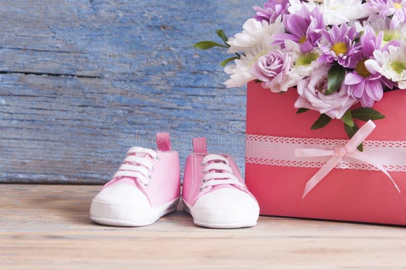 Kleine Kinderschuhe und schöner Blumenblumenstrauß auf dem hölzernen Vorsprung lizenzfreies stockbild