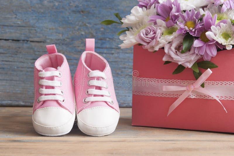 Kleine Kinderschuhe und schöner Blumenblumenstrauß auf dem hölzernen Vorsprung lizenzfreie stockbilder