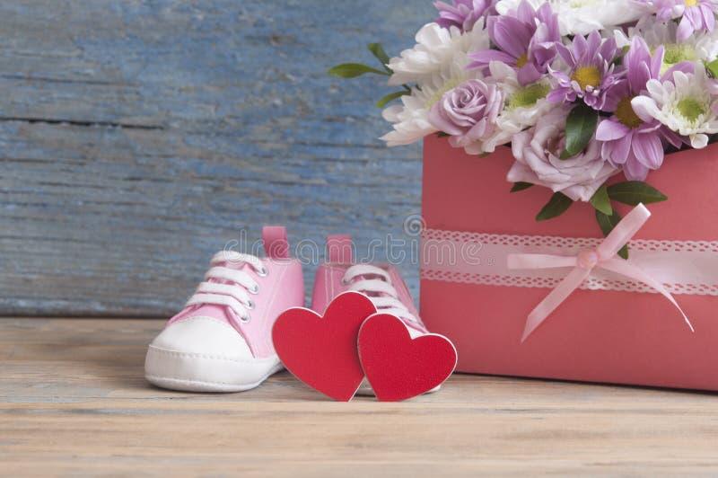 Kleine Kinderschuhe und schöner Blumenblumenstrauß auf dem hölzernen Vorsprung stockfotos