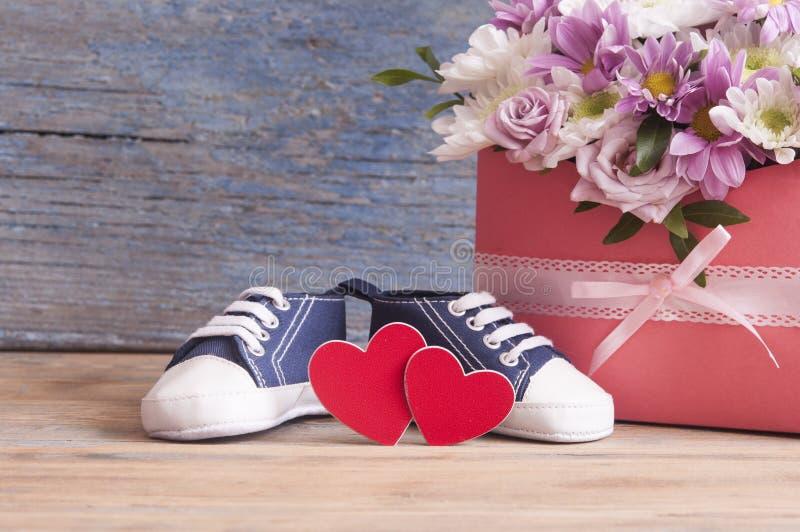 Kleine Kinderschuhe und schöner Blumenblumenstrauß auf dem hölzernen Vorsprung lizenzfreie stockfotos