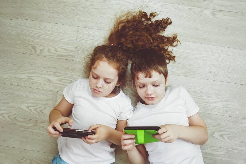 Kleine Kinderspiel mit Smartphone lizenzfreies stockbild