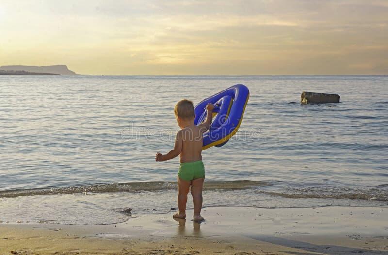 Kleine kleine kindjongen die naar het strand van de zee-zee van de zee-zee loopt bij de avondzonsondergang die ver weg kijkt royalty-vrije stock afbeeldingen
