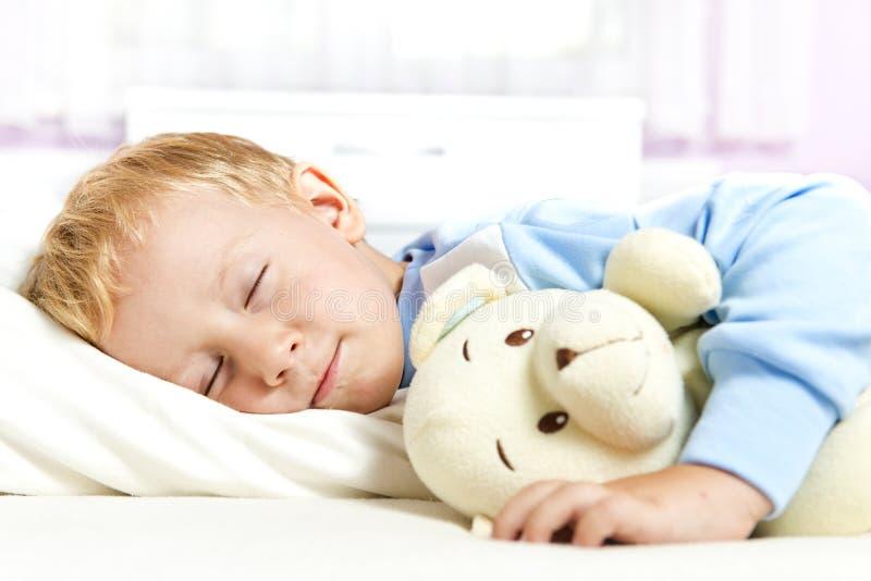 Kleine kindslaap in bed stock foto's
