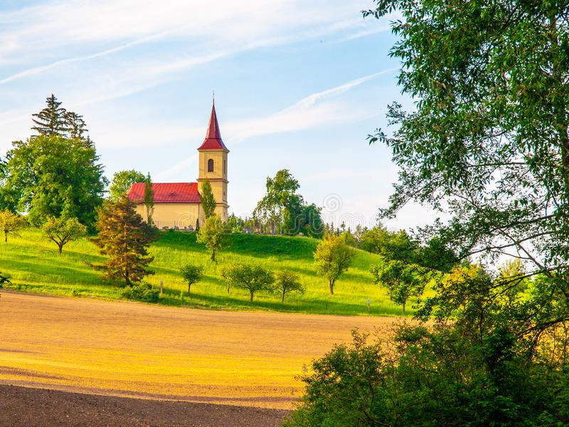 Kleine Kirche mitten in üppiger grüner Frühlingslandschaft am sonnigen Tag St- Peter und Pauls-Kirche bei Bysicky nahe Lazne stockfotografie