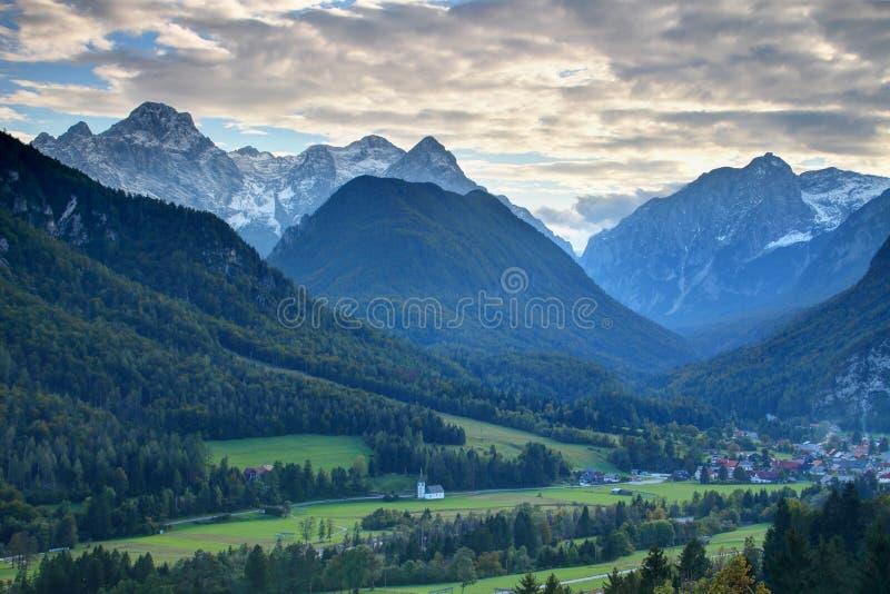 Kleine Kirche und slowenisch Dorf mit Julian Alps hinten stockfotografie
