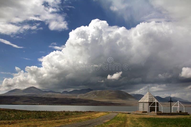 Kleine Kirche unter einer enormen weißen Wolke im Dorf von Foka stockfotos