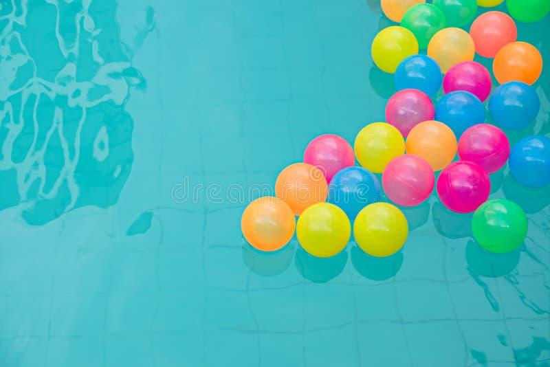 Kleine kleurrijke strandballen die in zwembad abstract concept drijven voor poolpartij royalty-vrije stock afbeelding