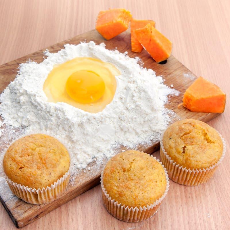 Kleine Kuchen, Mehl und Ei auf Küchentisch stockfotografie