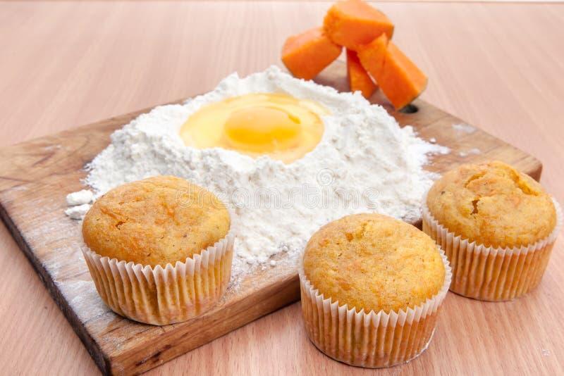 Kleine Kuchen, Mehl und Ei auf Küchentisch stockbilder