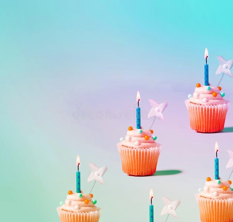 Kleine Kuchen mit beleuchteten Kerzen lizenzfreie abbildung