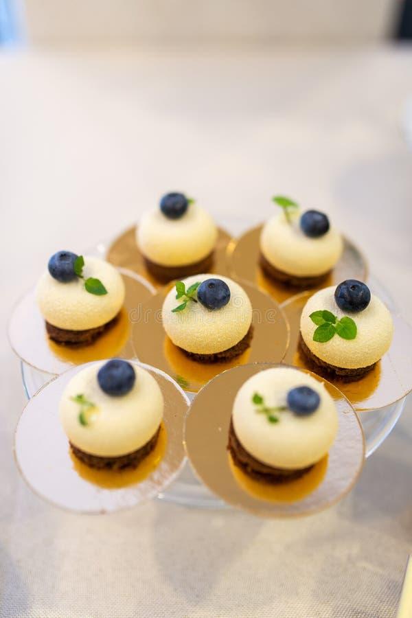 Kleine Kuchen mit Blaubeere auf Bankettisch Platzieren Sie BouquetBride der Braut und pflegen Sie Tabelle mit Blumenstrauß der Br stockfotografie