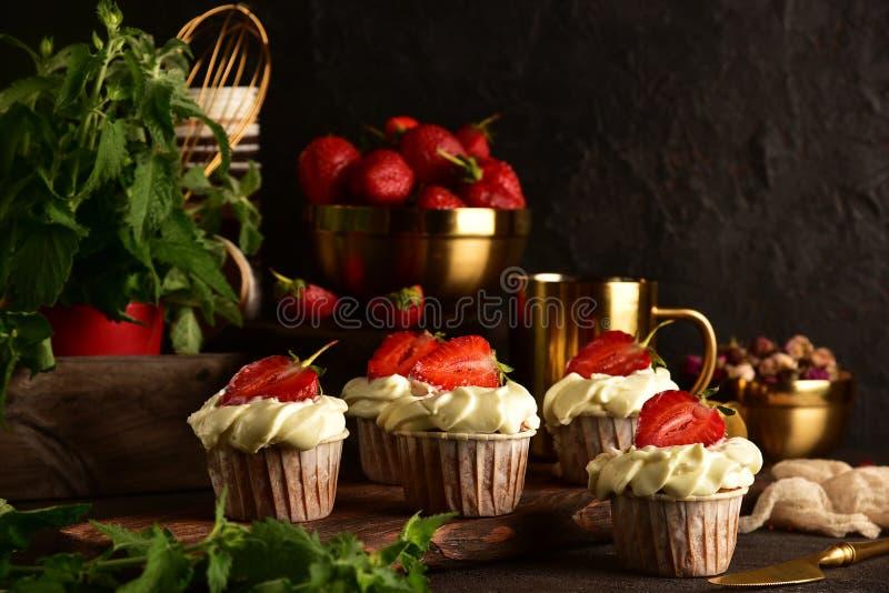 Kleine Kuchen mit Erdbeeren auf einem dunklen Hintergrund Noch Leben 1 lizenzfreies stockfoto