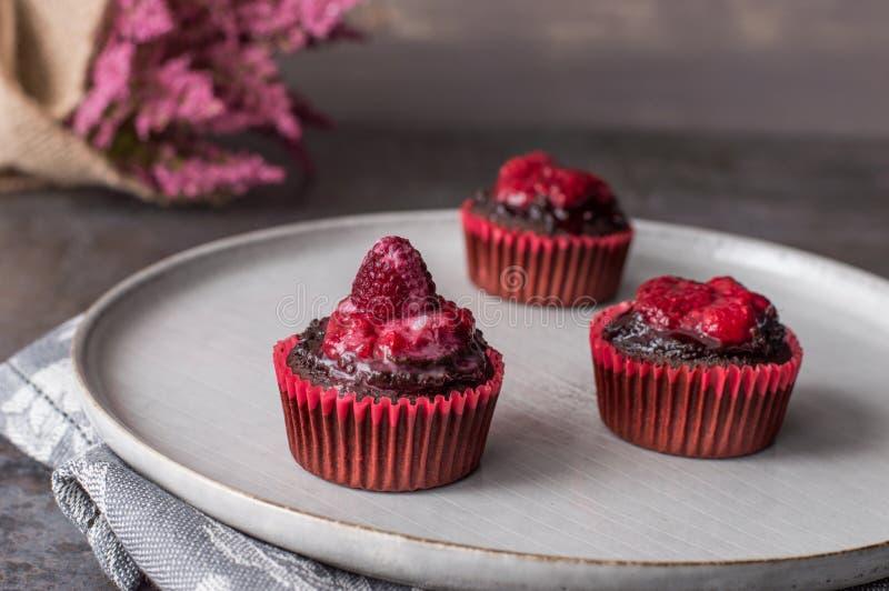 Kleine Kuchen mit Himbeerschokoladenbelag lizenzfreies stockbild