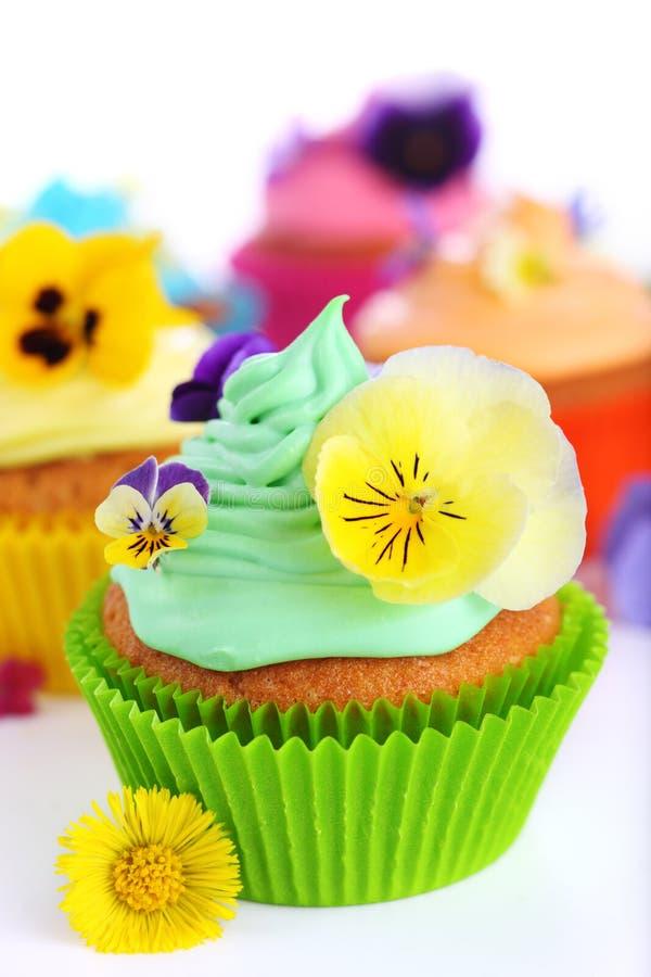 Kleine Kuchen mit Sahne und Veilchen stockfoto