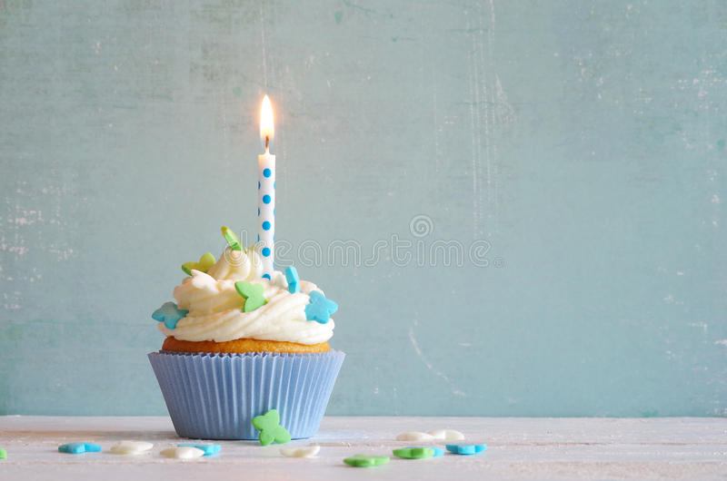 Kleine Kuchen mit Sahne und Zuckerbutterflys und Geburtstagskerze lizenzfreies stockbild