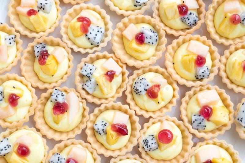 Kleine Kuchen verziert mit frischen Früchten pitaya, Ananas und Melone stockfotografie