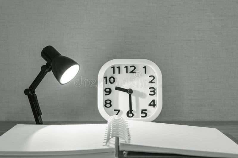 Kleine Lampe der Nahaufnahme mit Licht mit unscharfem Buch und weißem Wecker auf hölzernem Schreibtisch maserte Hintergrund im Sc stockbild