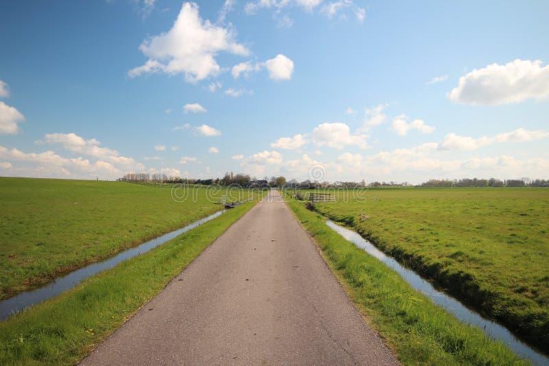 Kleine landweg langs een dijk in Zoeterwoude in Nederland stock afbeelding