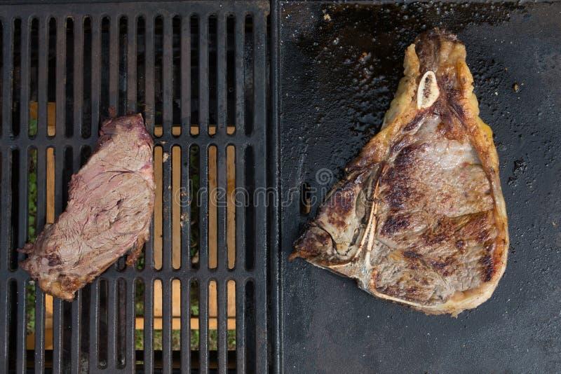Kleine lapjes vlees tegenover groot Rundvleeslapje vlees op het grillconcept lage klein als het Europese Amerikaanse voedsel eten royalty-vrije stock foto