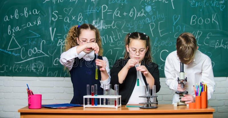 Kleine lege flessen Chemieonderwijs studenten die biologieexperimenten met microscoop doen Het kleine jonge geitjes leren stock foto's