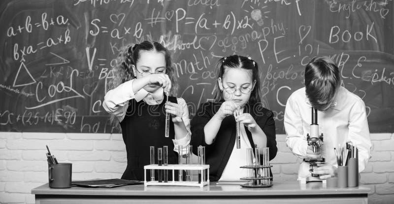 Kleine lege flessen Chemieonderwijs studenten die biologieexperimenten met microscoop doen Het kleine jonge geitjes leren royalty-vrije stock afbeelding