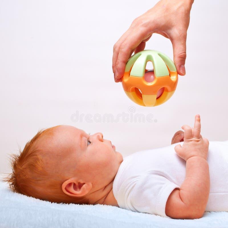 Kleine leggende baby met stuk speelgoed stock afbeelding