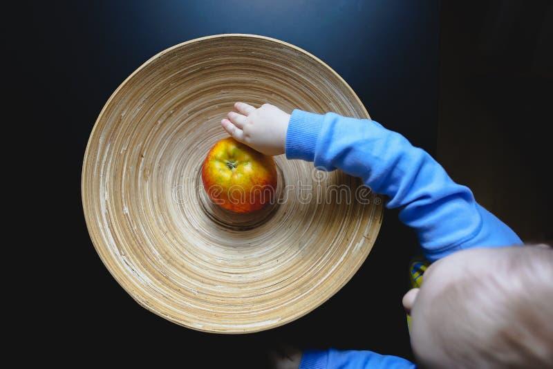 Kleine leuke babyholding in handen originele houten plaat met één appel Organisch, natuurlijk materiaal van kom met ononderbrok royalty-vrije stock foto's