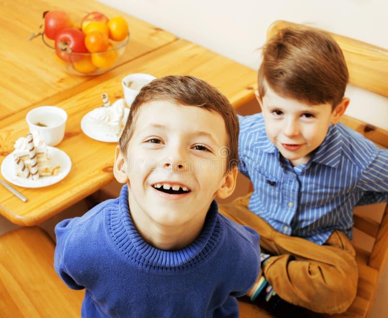 Kleine leuke jongens die dessert op houten keuken eten Het binnenland van het huis stock foto's