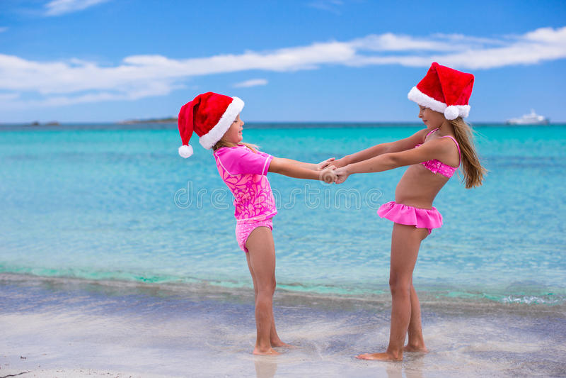 Kleine leuke meisjes in Kerstmanhoeden die pret hebben  stock foto