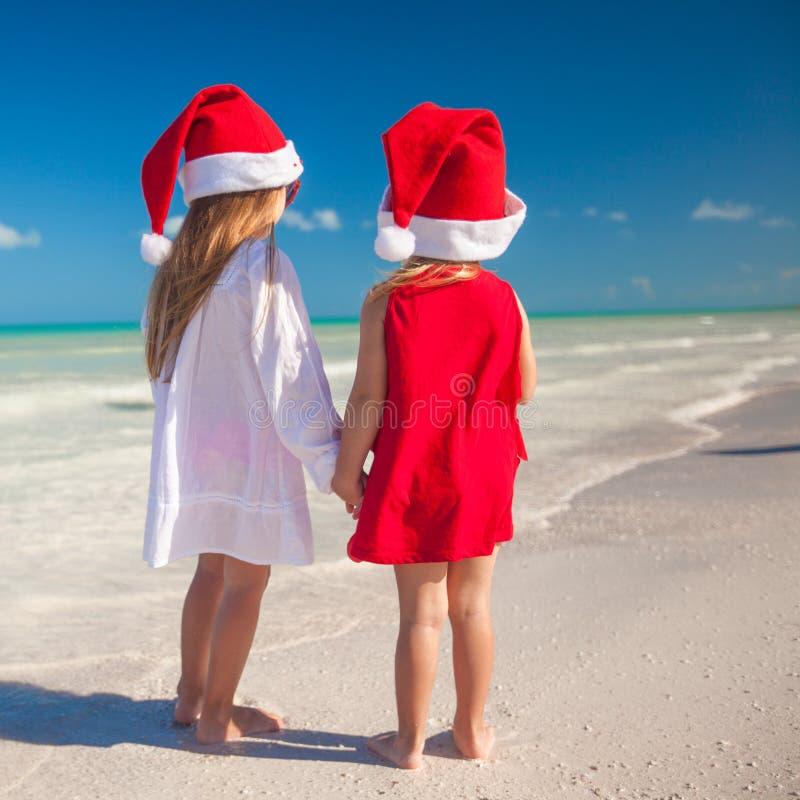 Kleine leuke meisjes in Kerstmishoeden op exotisch stock fotografie