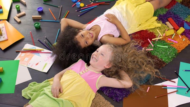 Kleine leuke multiraciale op tapijt liggen en vrienden die, gelukkige kinderjaren lachen royalty-vrije stock afbeeldingen