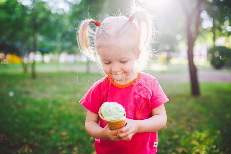 Kleine lustige Mädchenblondine, die süße blaue Eiscreme in einer Waffelschale auf einem grünen Sommerhintergrund im Park isst ges lizenzfreies stockbild