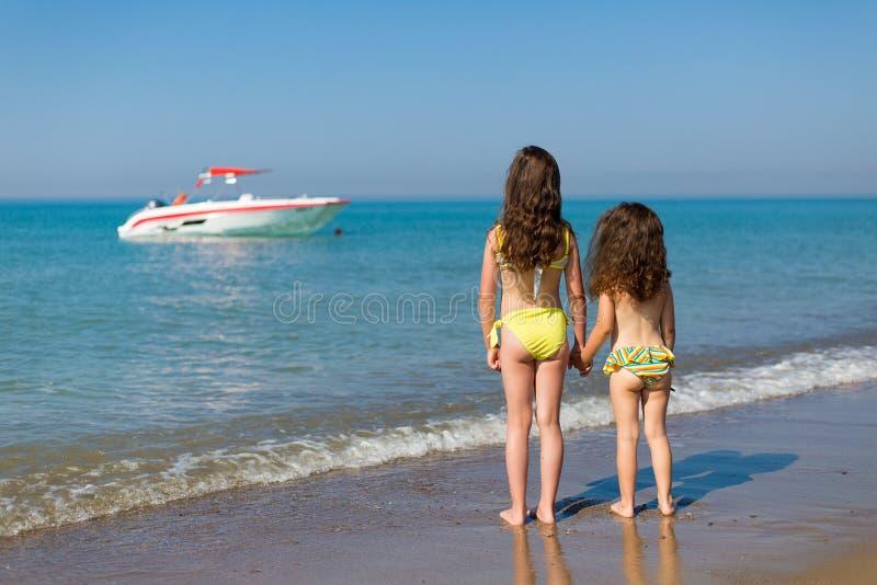 Kleine Mädchen in den Badeanzügen auf dem Strand, der zurück steht und im Urlaub das Boot in den Meerkindern betrachtet stockbild
