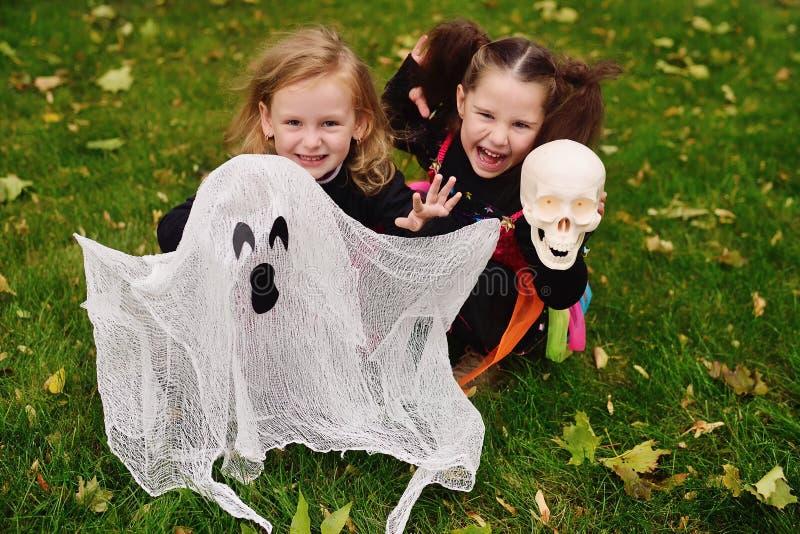 Kleine Mädchen in den Karnevalskostümen von Hexen für Halloween mit einem Spielzeuggeist im Park auf einem Hintergrund des Herbst stockfoto