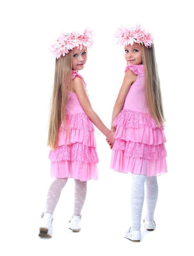 Kleine Mädchen in den rosafarbenen Kleidern stockfoto