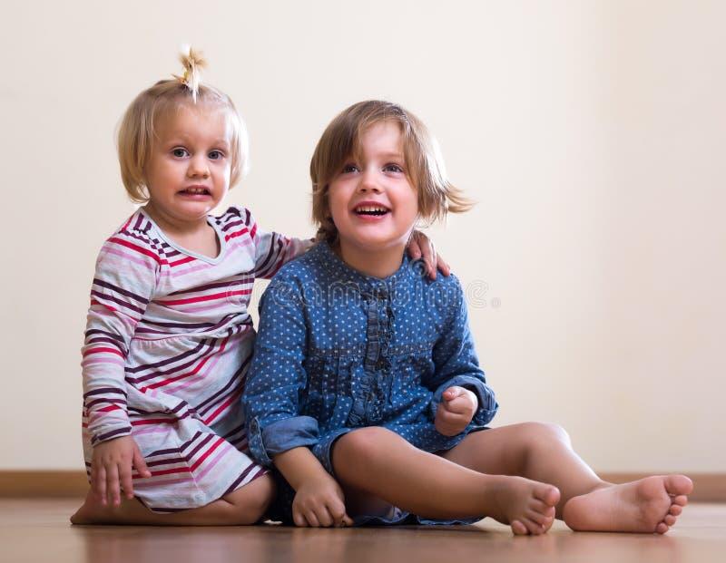 Kleine Mädchen, die auf Boden sitzen stockbild