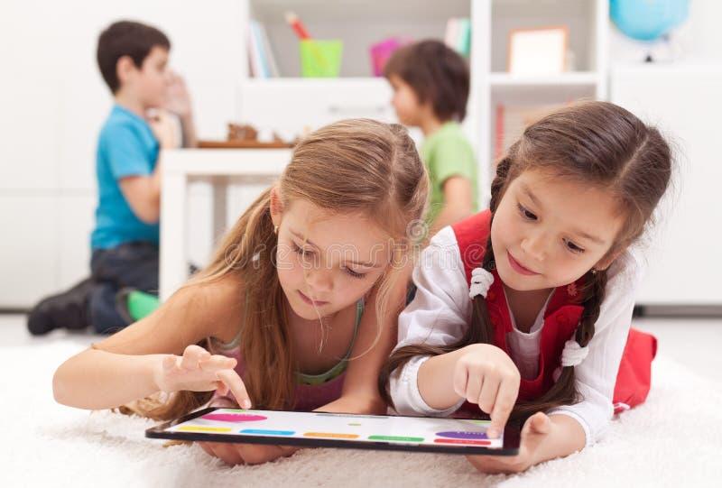 Kleine Mädchen, die auf einer rechneneinheit der Tablette spielen stockfoto
