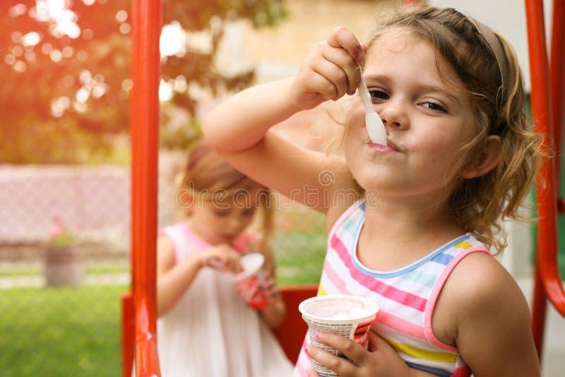 Kleine Mädchen, die draußen Eiscreme essen lizenzfreie stockfotografie