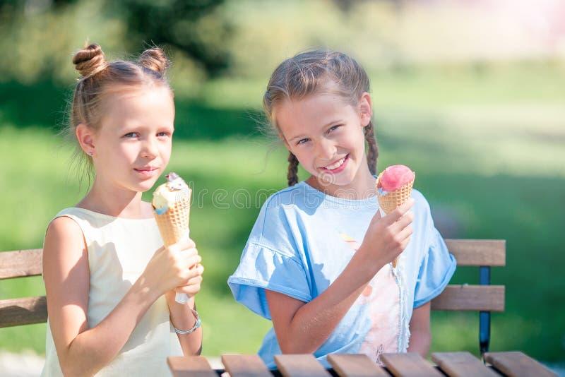 Kleine Mädchen, die draußen Eiscreme am Sommer Café im im Freien essen stockfotos