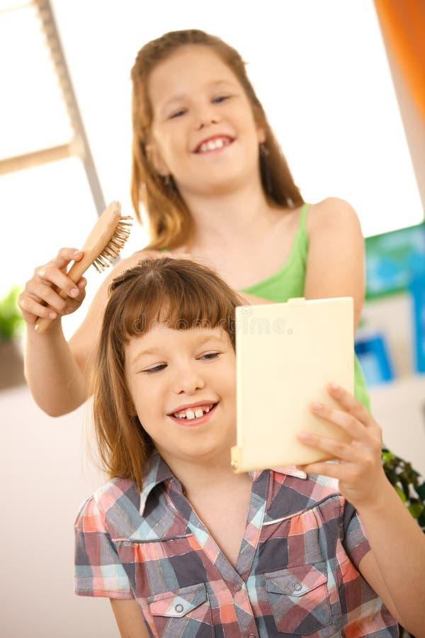 Kleine Mädchen, die Friseur spielen lizenzfreie stockbilder