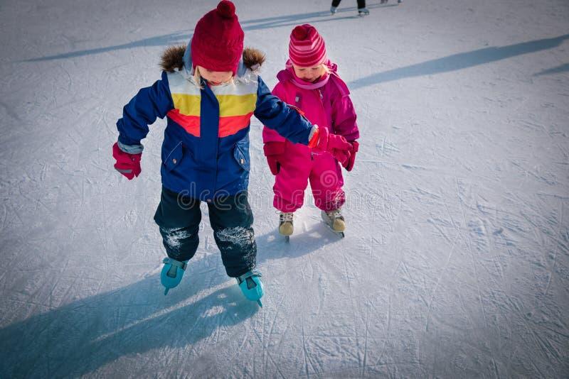 Kleine Mädchen, die im Schnee gemeinsam Ski laufen, Kinder Winteraktivitäten lizenzfreie stockbilder