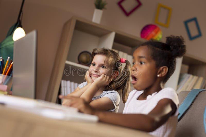 Kleine Mädchen, die Karikaturen aufpassen stockbilder