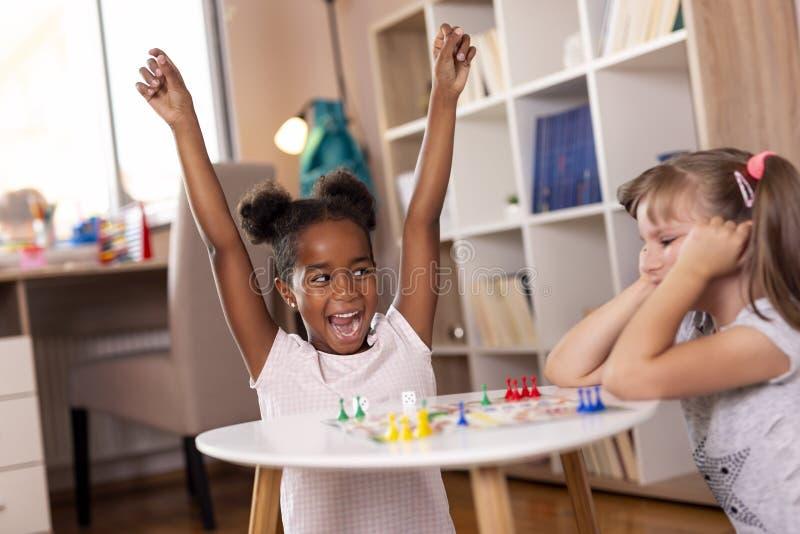 Kleine Mädchen, die Ludo-Brettspiel spielen lizenzfreies stockfoto
