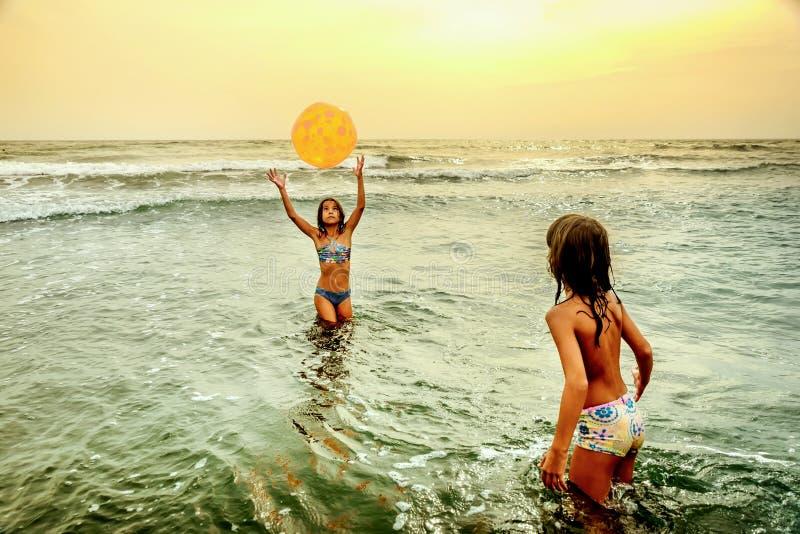 Kleine Mädchen, die mit dem Ball im Ozean spielen lizenzfreies stockbild