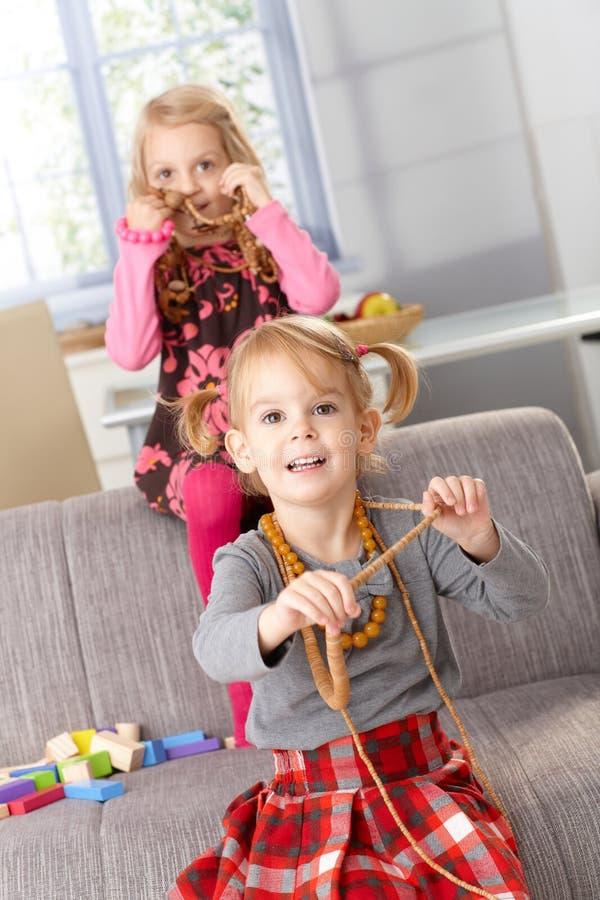 Kleine Mädchen, die mit Halsketten des Mutter spielen lizenzfreie stockfotografie
