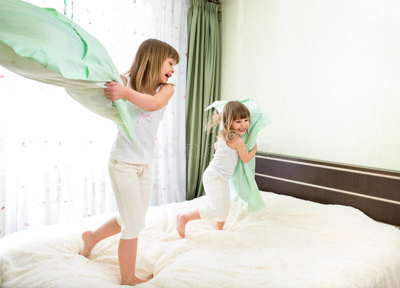 Kleine Mädchen, die mit Kissen im Schlafzimmer kämpfen lizenzfreie stockfotos