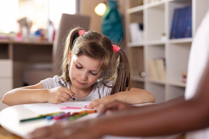 Kleine Mädchen, die mit Zeichenstiften zeichnen stockbilder