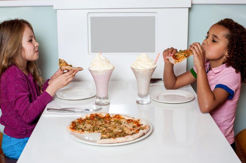 Kleine Mädchen, die Pizza in einem Restaurant genießen stockfoto