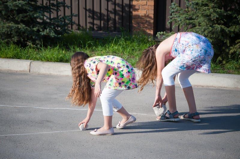 Kleine Mädchen, die zusammen draußen zu Hause an einem Sommertag spielen lizenzfreie stockfotografie