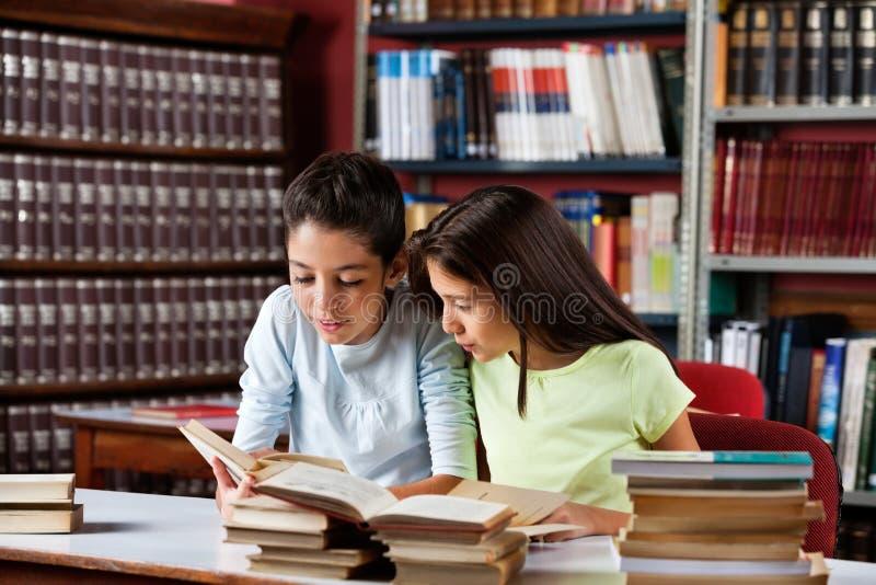 Kleine Mädchen-Lesebuch zusammen in der Bibliothek lizenzfreies stockbild